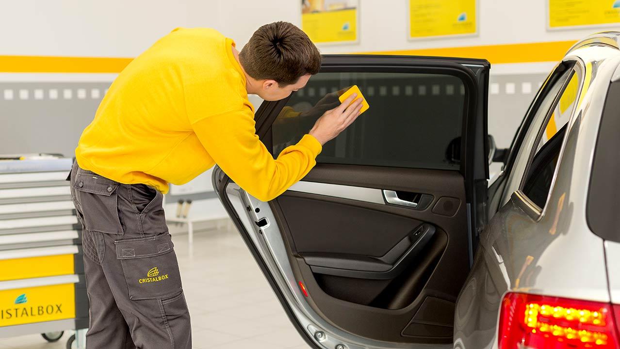 Técnico aplicando servicio de laminado o tintado de lunas en un coche