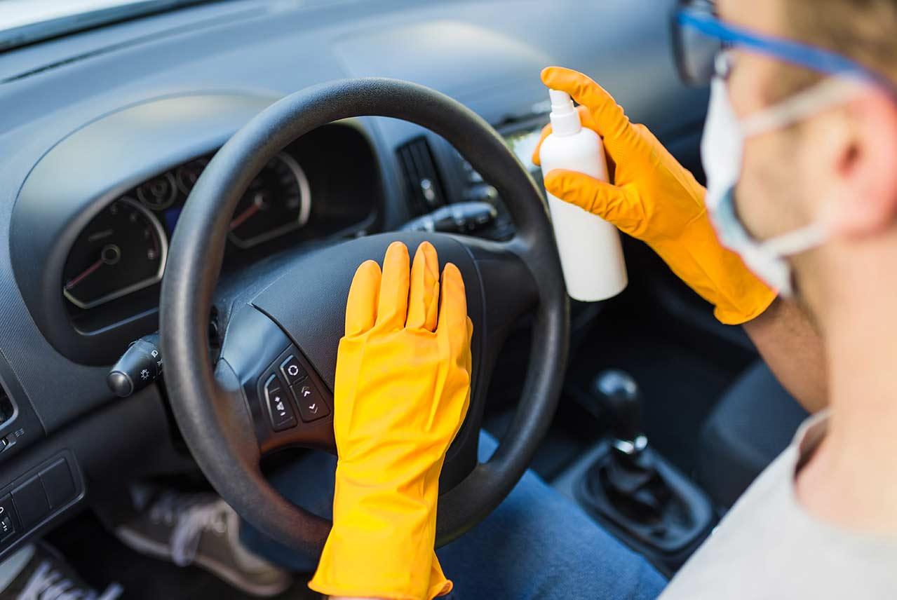 Conductor desinfectando el interior de un coche en casa utilizando todas las medidas de seguridad frente a la Covid.19