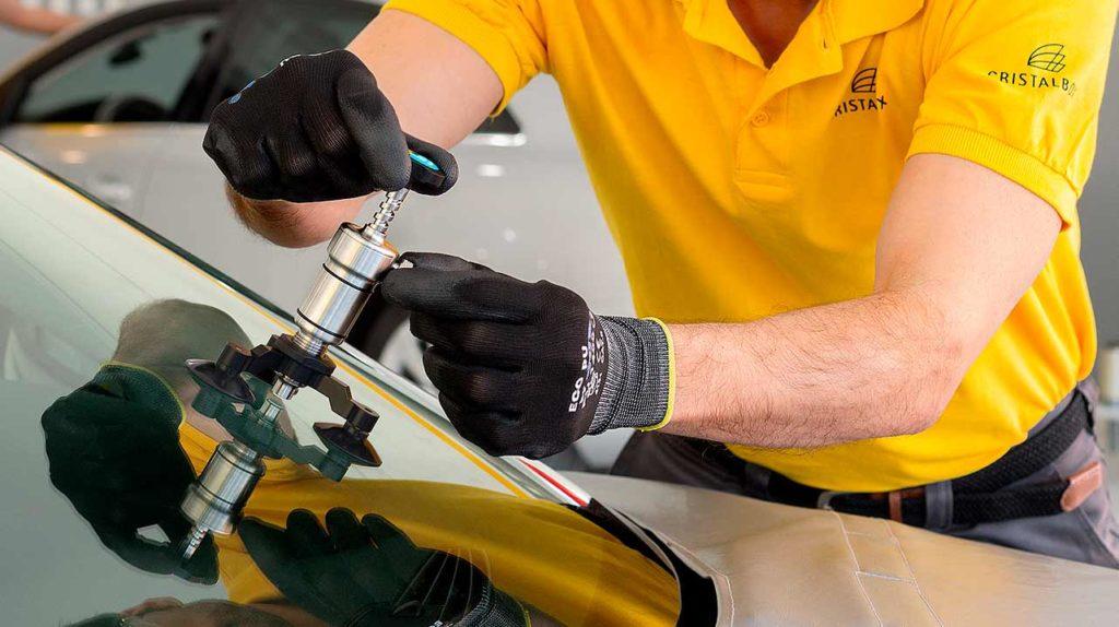 Técnico en un taller reparando un parabrisas que ha sufrido un golpe o raja