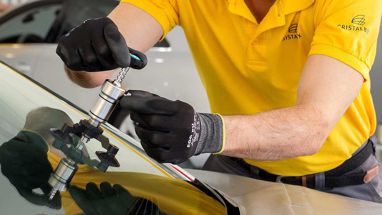 Técnico reparando una luna luna rota en el servicio de arreglar parabrisas en el taller.